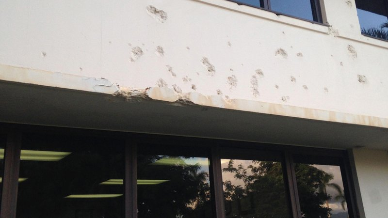 The exterior of PACAF headquarters is still pocked with bullet holes.