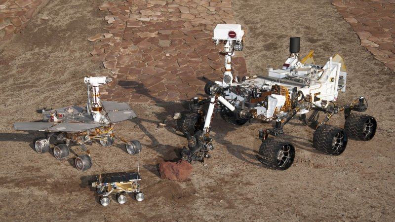 Three generations of NASA's Mars rovers from 1997 to 2012, photographed inside the Mars Yard at the Jet Propulsion Lab in Pasadena, Calif: flight spare for Sojourner (front), Mars Exploration Rover Project test rover (left) and Curiosity test rover (right).