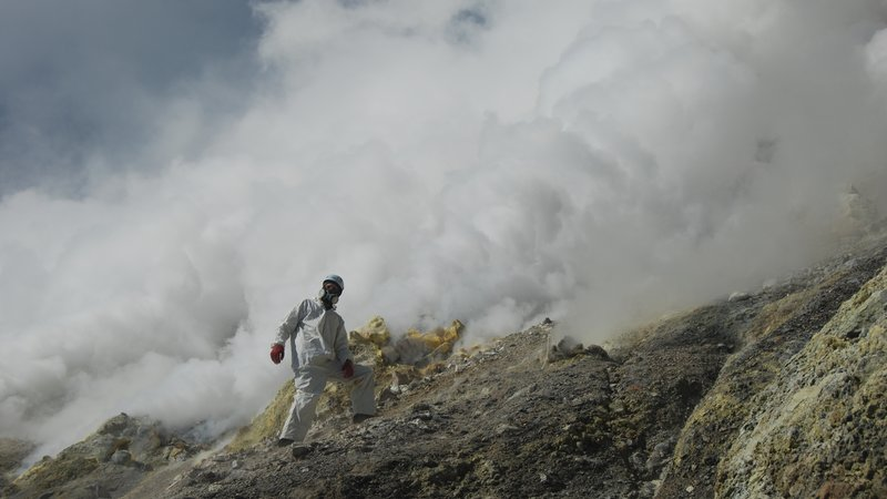 Volcanologist Tobias Fischer of the University of New Mexico hikes down the steep crater wall of the vigorously degassing Gareloi volcano in the Western Aleutian Islands to collect a volcanic gas sample.