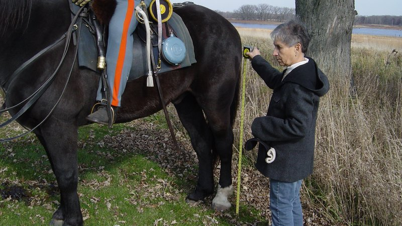 Frances B. Hicks, Jim's wife, takes measurements to calculate travel time via a horse.