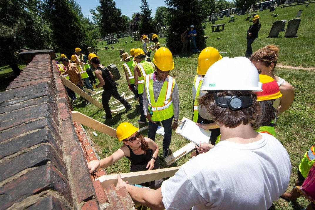 Participants executing simple shoring in order to stabilize a brick wall at Congressional Cemetery. (Michael Barnes, Smithsonian)