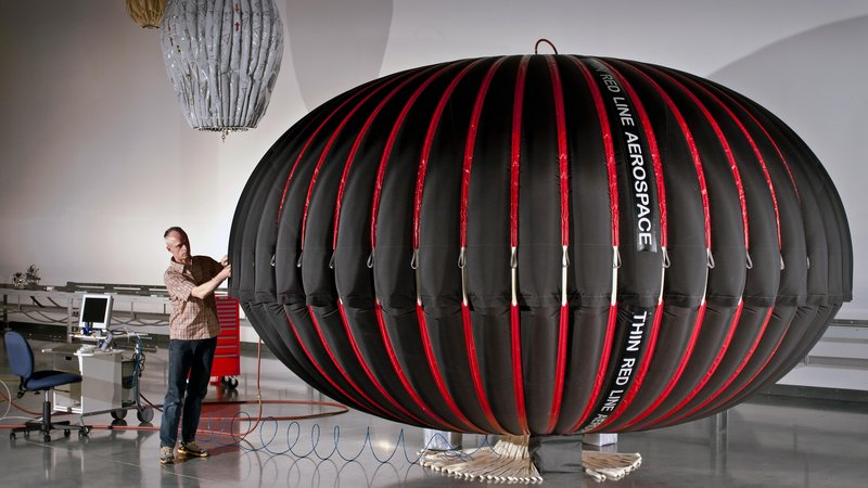 """Thin Red Line Aerospace Chief Engineer and CEO Maxim de Jong inspects a UW-CAES """"Energy Bag"""" during initial test inflation"""