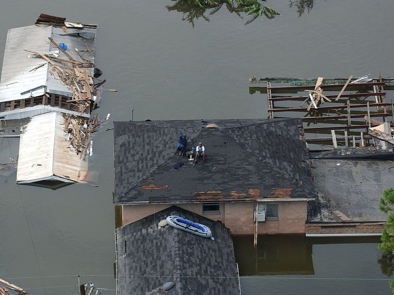 People sit on a roof waiting to be rescued after Hurricane Katrina