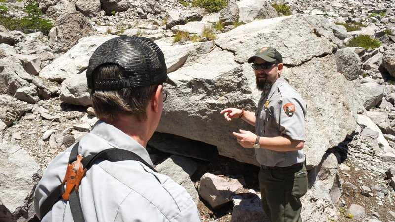 Magnuson and Jason Mateljak (right), general natural resources manager at Lassen, stand by a pika burrow they have identified by traces of scat.