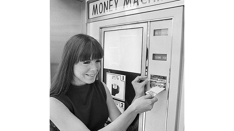 A woman makes use of an early model automated teller machine belonging to Surety National Bank in 1970.
