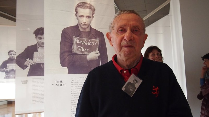 Tibor Sands stands in front of the photo taken of him at Kloster Indersdorf in 1946.