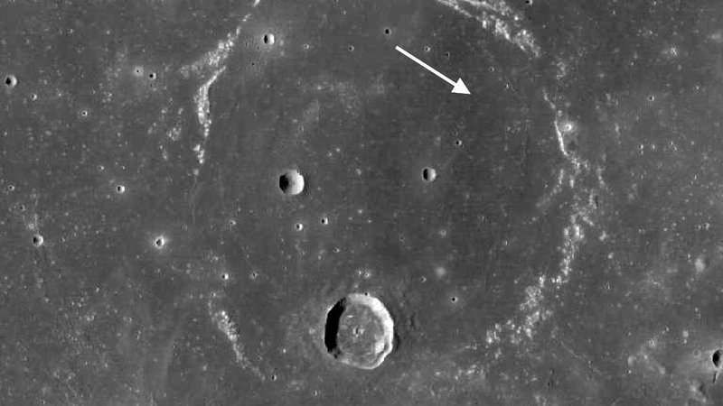 The Lunar Reconnaissance Orbiter's Wide Angle Camera returned this view of the ghost ring of Flamsteed P. The arrow shows the location of the Surveyor 1 lander.