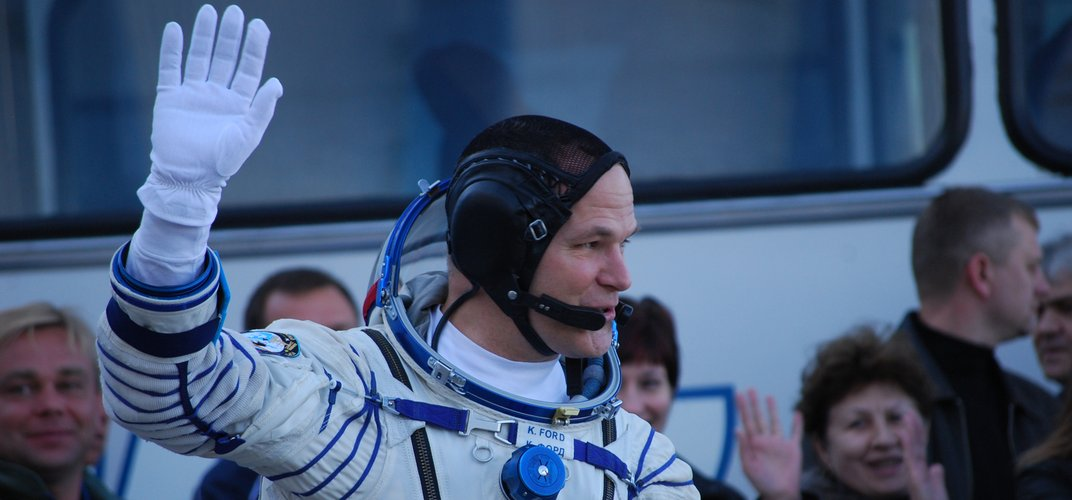 A Russian cosmonaut waves to onlookers