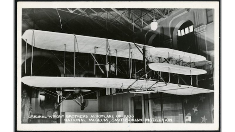 A black and white  photo postcard depicts the 1903 Wright Flyer hanging on display in the Arts and Industries Building, where it was on view from 1948 to 1976, before it was moved to the National Air and Space Museum. Photo courtesy of the Smithsonian Ins