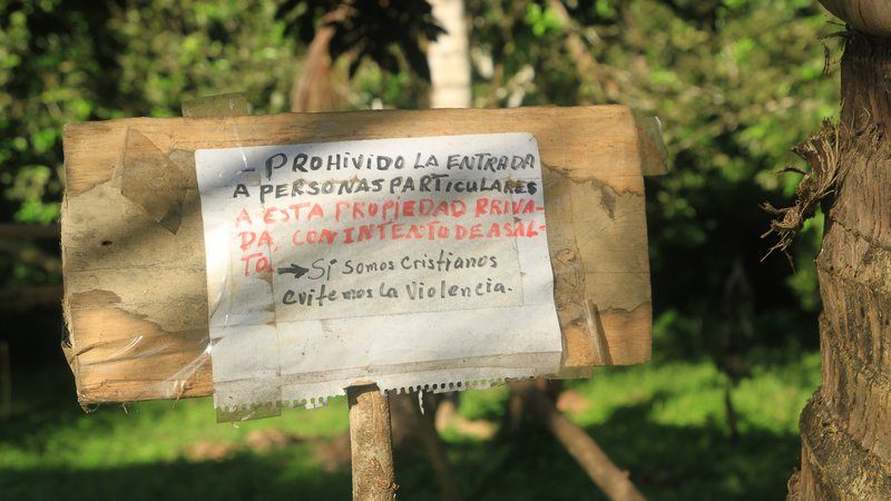 """A sign in front of an indigenous farm in rural Honduras that was eventually overrun by traffickers. It reads, """"The entry of persons with violent intent is prohibited. Yes we are Christians and we avoid violence."""""""