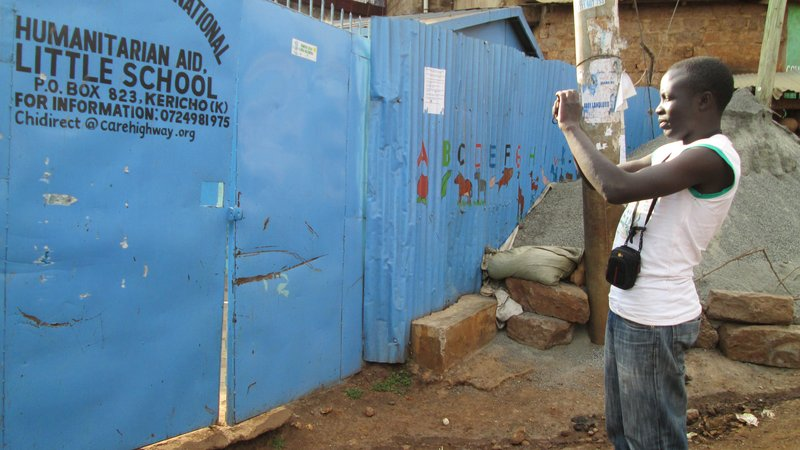 Steve Banner of Map Kibera Trust photographs a school in Kibera, Nairobi, Kenya.