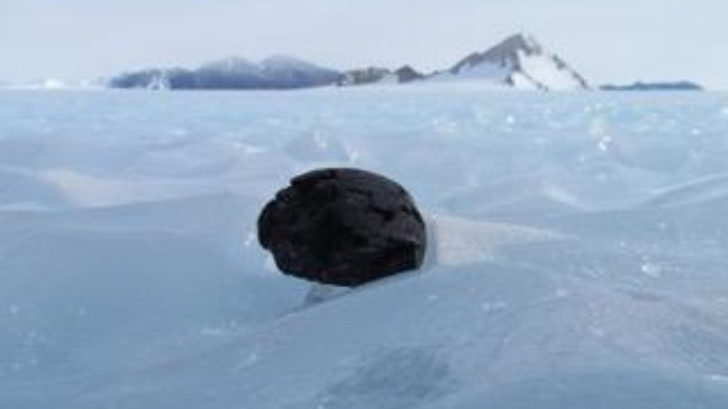 A meteorite sits on the surface of ice in a meteorite stranding zone in the Transantarctic mountains.