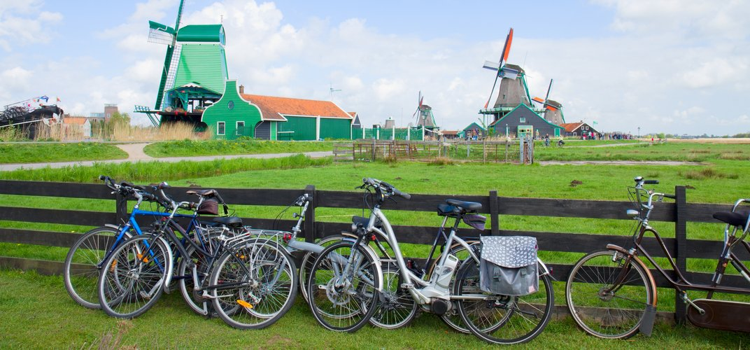 Traditional Dutch landscape of countryside, windmills, and bicycles