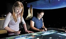 Visitors assemble space station elements in the Moving Beyond Earth gallery.