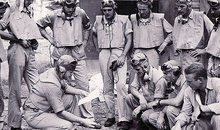 At the Black Sheep Squadron's base on the South Pacific island of Espiritu Santo, Boyington (holding paper) briefs his pilots on an upcoming mission.