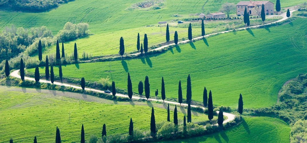 The quintessential Tuscan landscape with rolling hills, cypress trees, and farmhouses