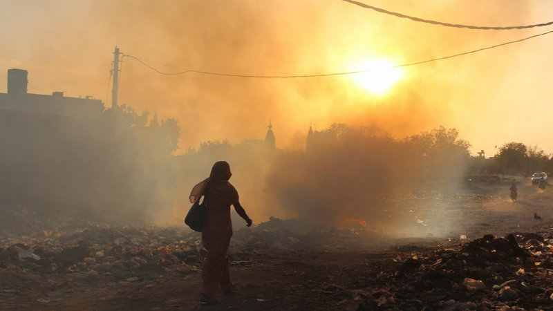 A woman walks past a garbage fire in East Delhi. Delhi's air pollution is the worst in the world, according to the World Health Organization.
