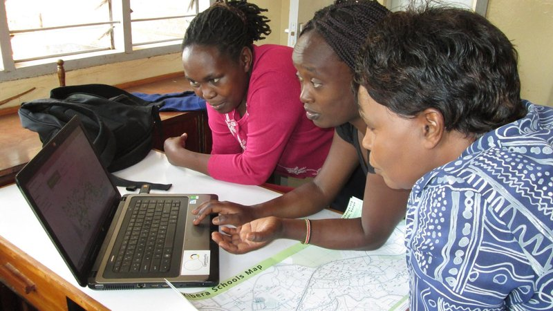 Lucy Fondo, center, of Map Kibera, shows two teachers how to use the community-driven mapping project that puts all of Kibera's schools on a map.