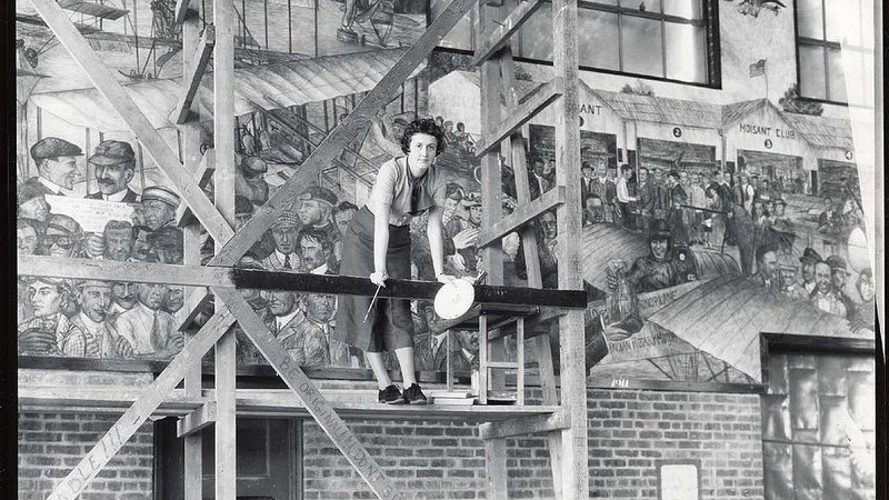 Rhonie painting her mural in Hangar F at Roosevelt Field in Long Island, New York. The mural is now at the Vaughn College of Aeronautics and Technology in Queens, New York.
